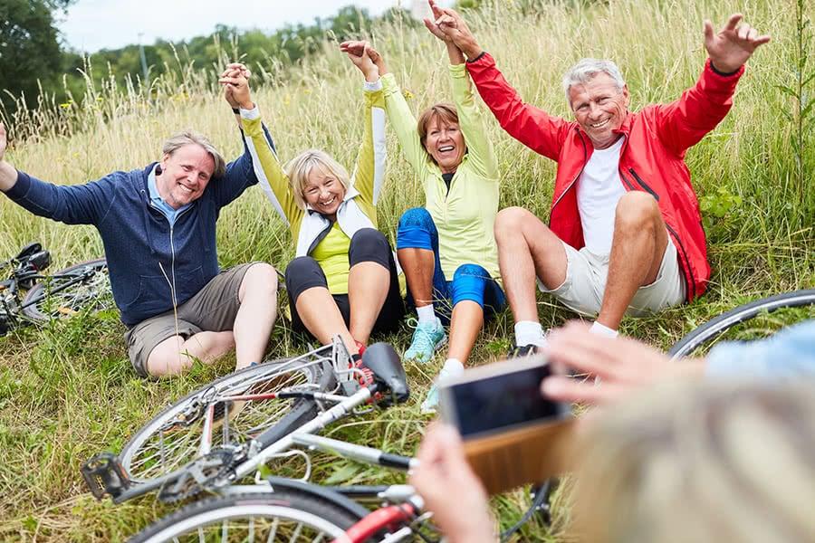 Vier Senioren sitzen im Gras in dem auch ihre Fahrräder liegen und jemand macht davon ein Foto mit einem Handy