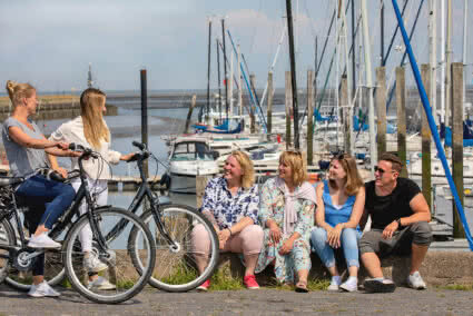 Drei Frauen und ein Mann sitzen auf einer kleinen Mauer an einem Yachthafen und gucken zwei Frauen mit ihren Fahrrädern an die neben ihnen stehen
