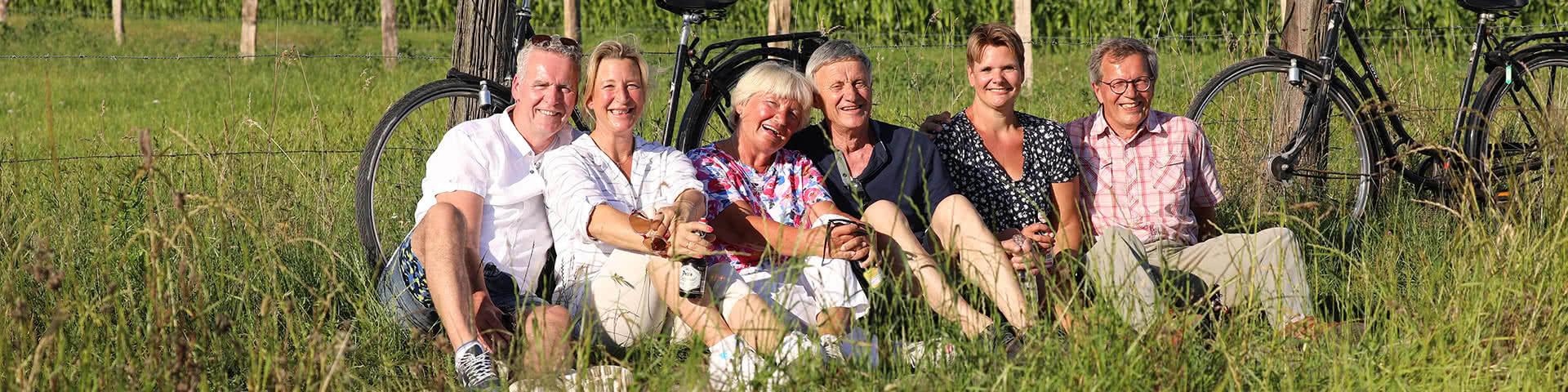 Drei Paare machen eine Pause von ihrer Radtour und sitzen auf einer Wiese