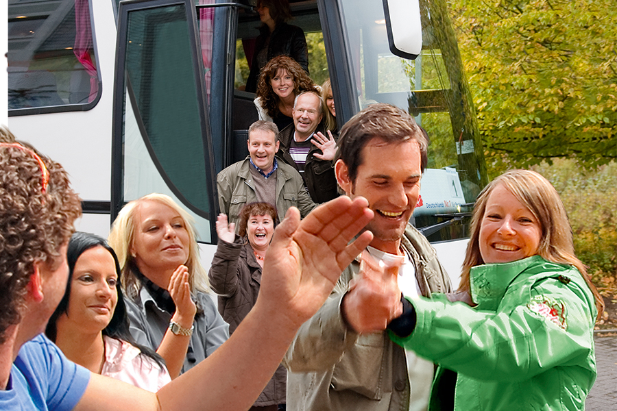 Feiernde Gruppe steigt aus einem Bus aus
