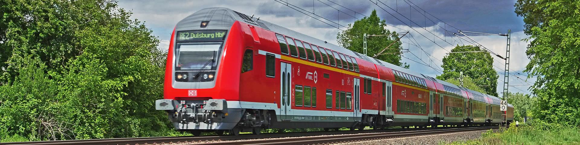 Zug der Deutschen Bahn auf Schienen mit Bäumen rechts und links
