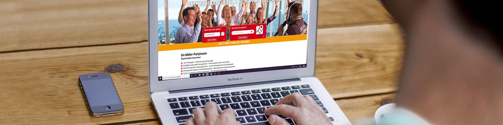 Ein Mensch sitz vor einem Laptop und surft auf der Müller-Touristik-Website
